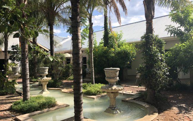 Cour intérieure du lodge Out of Africa en Namibie avec fontaine et palmiers