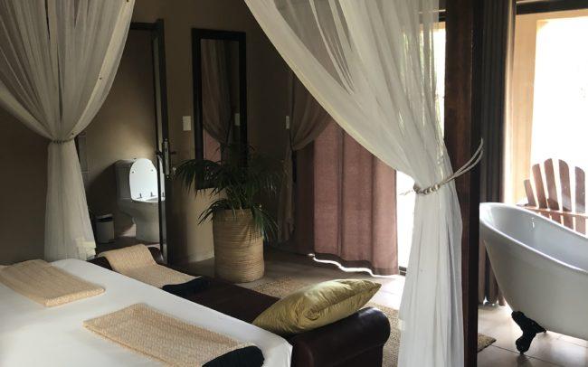 Ma chambre au Toshari Lodge. Très belle chambre avec un immense lit à baldaquin, sa baignoire îlot devant la baie vitrée, salle de douche séparée et son coin réfrigérateur, café et thé. Une belle terrasse équipée d'une table basse et de deux chiliennes en bois avec vue sur la savane africaine.