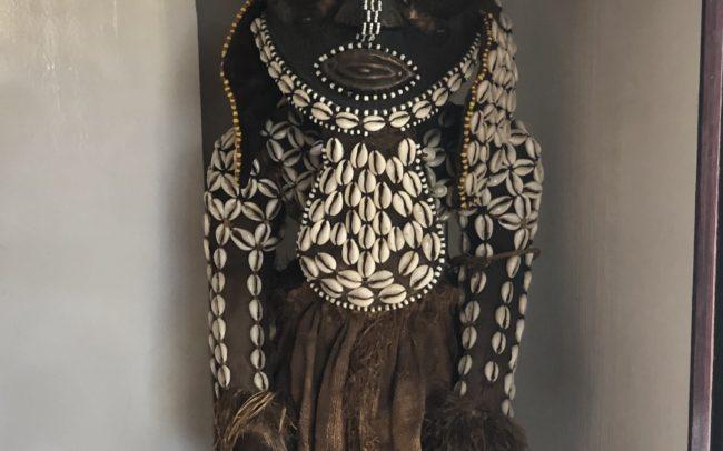 Objet déco art africain, statuette en bois et ornée de coquillages et de fibres naturelles